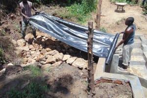 The Water Project: Mukangu Community, Metah Spring -  Laying Of Tarp