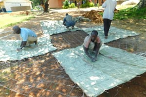 The Water Project: Hobunaka Primary School -  Tying Sugar Sacks To Dome Wire