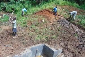 The Water Project: Maondo Community, Ambundo Spring -  Soil Backfilling Over Tarp