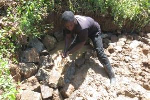 The Water Project: Tumaini Community, Ndombi Spring -  Stone Backfilling