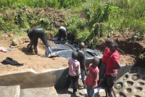 The Water Project: Tumaini Community, Ndombi Spring -  Adding Plastic Tarp Over Stones