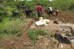 The Water Project: Tumaini Community, Ndombi Spring -  Digging Cut Off Drainage