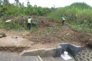 The Water Project: Tumaini Community, Ndombi Spring -  Soil Backfilling