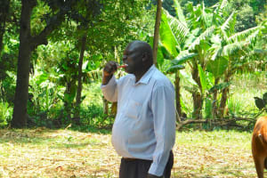 The Water Project: Namarambi Community, Iddi Spring -  Man Demonstrates Toothbrushing