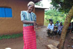 The Water Project: Musiachi Community, Mutuli Spring -  Woman Demonstrates Handwashing