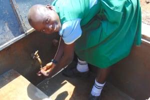 The Water Project: Bumbo Primary School -  Student Enjoying Rain Tank Water