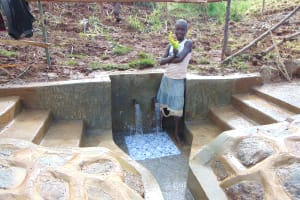 The Water Project: Musiachi Community, Mutuli Spring -  Girl Holding Twigs To Clean Spring