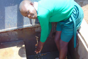 The Water Project: Bumbo Primary School -  Student Enjoying Tank Water