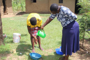 The Water Project: Tumaini Community, Ndombi Spring -  Betty Pours Water For Handwashing Volunteer