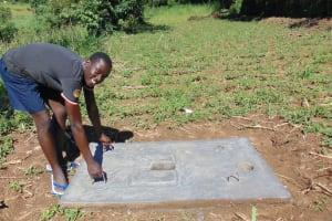 The Water Project: Emurumba Community, Makokha Spring -  Showing Off Latrine Slab Portability