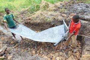 The Water Project: Emurumba Community, Makokha Spring -  Adding Tarp To Foundation