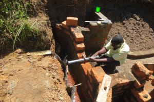The Water Project: Tumaini Community, Ndombi Spring -  Pipe Setting