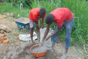 The Water Project: Emurumba Community, Makokha Spring -  Community Members Help Mix Cement