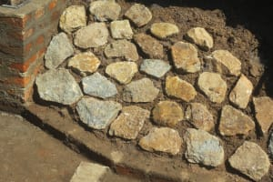 The Water Project: Tumaini Community, Ndombi Spring -  Rub Wall Stone Pitching