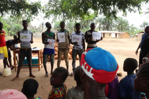 The Water Project: Kamayea, Susu Community & Church -  Participants Hold Up Posters