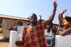 The Water Project: Lungi, 25 Maylie Lane -  Community Member Rejoicing Holding Clean Water