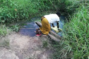 The Water Project: Kaitabahuma I Community -  Fetching Water From Broken Down Spring Protection