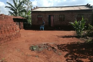 The Water Project: Kabo Village -  Woman Stands In Her Compound