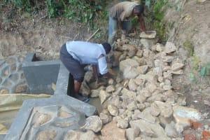 The Water Project: Bukhaywa Community, Ashikhanga Spring -  Backfilling With Stones