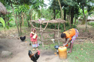 The Water Project: Litinye Community, Shivina Spring -  Beatrice Cleans Utensils Next To Dishrack And Daughter Joy