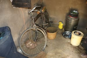 The Water Project: Mukhuyu Community, Chisombe Spring -  Storage Container And A Bicycle Inside The Kitchen