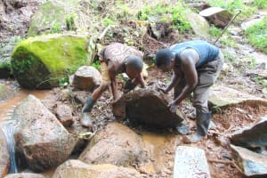 The Water Project: Chepnonochi Community, Shikati Spring -  Moving Stones Into Backfilled Area