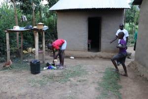 The Water Project: Mukhonje Community, Mausi Spring -  A Boy Washing Utensils