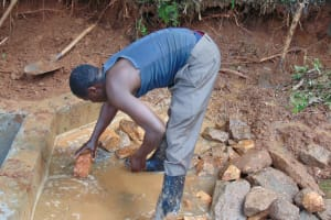 The Water Project: Chepnonochi Community, Shikati Spring -  Backfilling With Stones