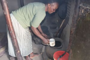 The Water Project: Mukhuyu Community, Chisombe Spring -  Grace Drawing Water From Storage Pot