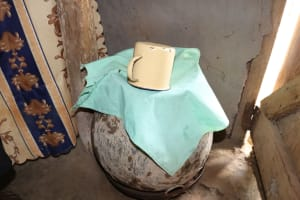 The Water Project: Mukhuyu Community, Chisombe Spring -  Water Storage Container Covered With Cloth And Cup