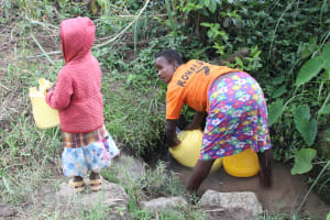 The Water Project: Litinye Community, Shivina Spring -  Beatrice Draws Water From Unprotected Spring