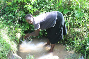 The Water Project: Litinye Community, Shivina Spring -  A Woman Waashing Hands At The Spring
