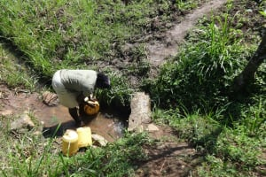 The Water Project: Mahira Community, Jairus Mwera Spring -  Washing Her Container Before Fetching Water