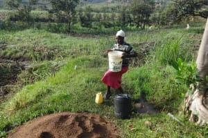 The Water Project: Mahira Community, Kusimba Spring -  Mounting Water On Head To Carry It Home