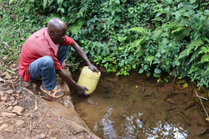 The Water Project: Harambee Community, Elijah Kwalanda Spring -  Rinsing Container Before Fetching Water