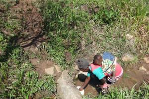 The Water Project: Mahira Community, Jairus Mwera Spring -  Alice Collects Water