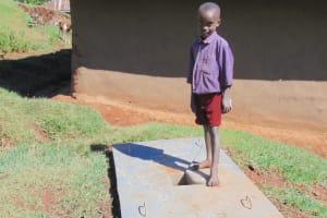 The Water Project: Chepnonochi Community, Shikati Spring -  A Boy With His Familys New Sanitation Slab