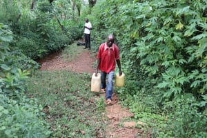The Water Project: Harambee Community, Elijah Kwalanda Spring -  Carrying Water From The Spring