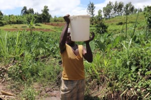 The Water Project: Mahira Community, Litinyi Spring -  Mounting Water On Head To Carry