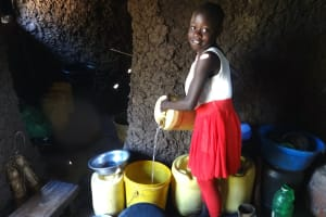 The Water Project: Mahira Community, Kusimba Spring -  A Child Pours Water Into Kitchen Storage Containers