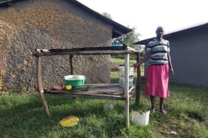 The Water Project: Mahira Community, Kusimba Spring -  A Woman Stands By Her Dishrack
