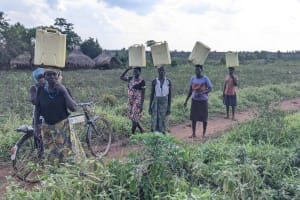 The Water Project: Alero B Community -  Mary Akumu In Black Blouse Carrying Water With The Family