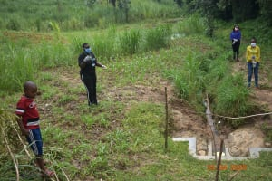 The Water Project: Emukoyani Community, Ombalasi Spring -  Staff Demonstrate Social Distancing