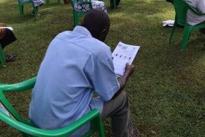 The Water Project: Shirakala Community, Ambani Spring -  A Community Member Reading Through The Manual