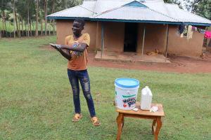 The Water Project: Elukuto Community, Isa Spring -  A Community Member Illustrates Handwashing At The Training