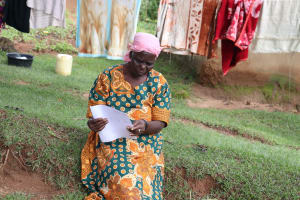 The Water Project: Lutali Community, Lukoye Spring -  An Elderly Woman Reading Through The Pamphlet
