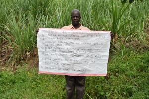 The Water Project: Musango Community, Emufutu Spring -  An Elder Holds The Caution Chart At The Spring