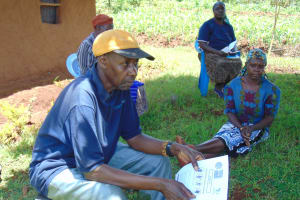 The Water Project: Visiru Community, Kitinga Spring -  Community Members Following Training With Pamphlets