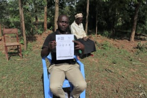 The Water Project: Ematetie Community, Weku Spring -  Showing His Pamphlet