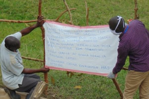The Water Project: Ulagai Community, Rose Obare Spring -  Installing Caution Chart At The Spring